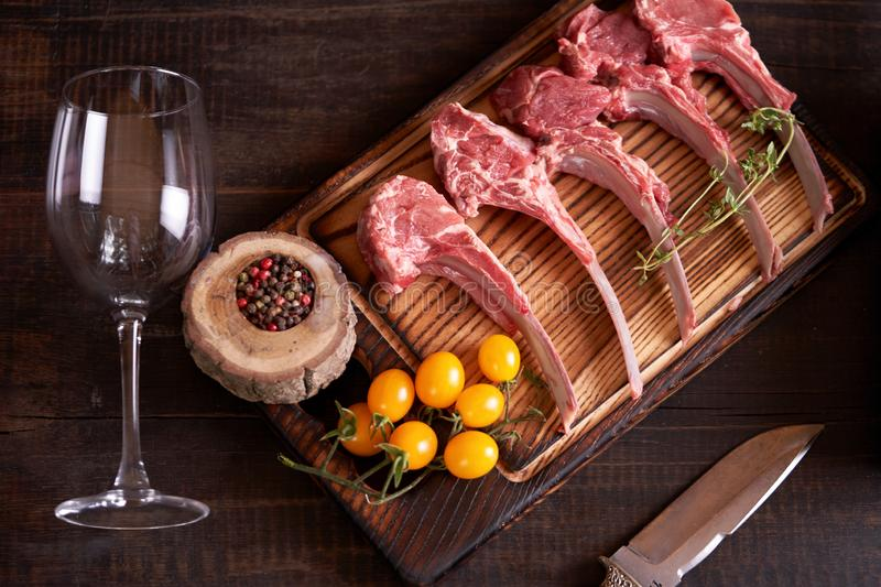 Cut raw rack of lamb on a cutting wooden board with yellow tomatoes, multi-colored peppercorns, and a wine glass lying next to it. Top view stock images