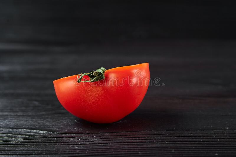 Cut red tomato on a black wooden background, food photography. Still life royalty free stock image