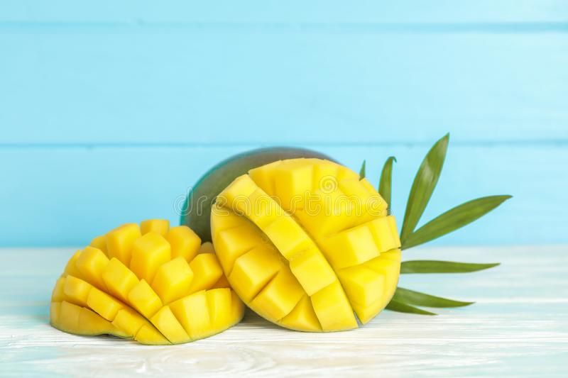 Cut ripe mangoes and palm leaf on white table against color background royalty free stock photos
