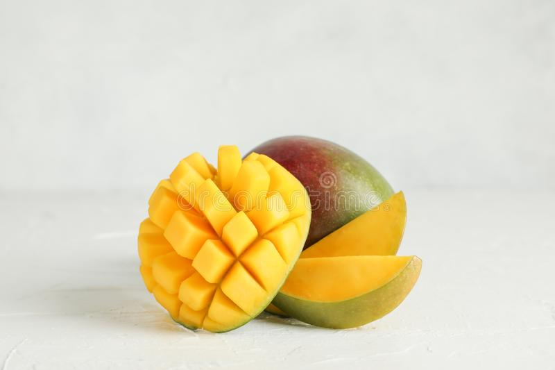 Cut ripe mangoes and space for text on white background royalty free stock photos
