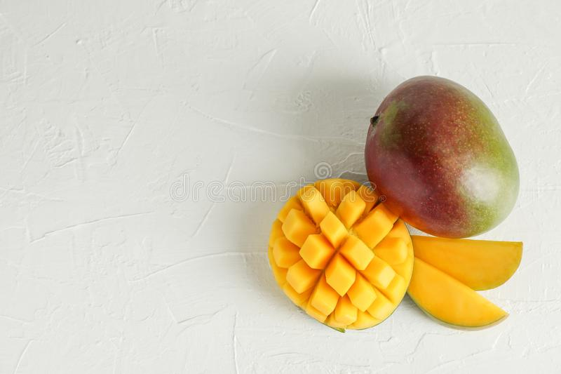 Cut ripe mangoes and space for text on white background royalty free stock photography