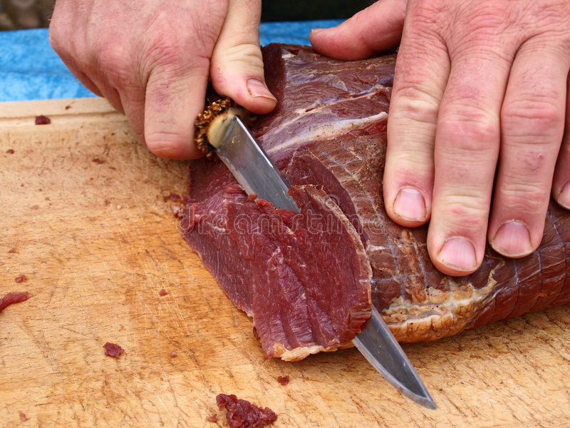 Cut roasted meat beef by a chef. Cut smoked roasted meat beef by a professional chef butcher stock photos
