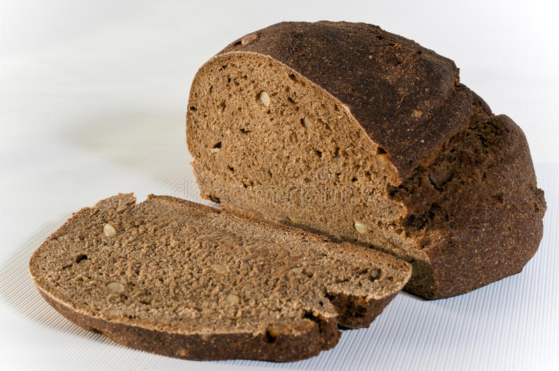 Cut rye bread. With pine nut on the white surface stock photography