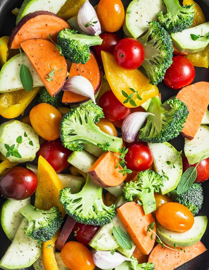 Cut seasonal raw vegetables - sweet potatoes, broccoli, bell peppers, zucchini, tomatoes, onions, garlic with spices, herbs. Cut seasonal raw vegetables - sweet royalty free stock image