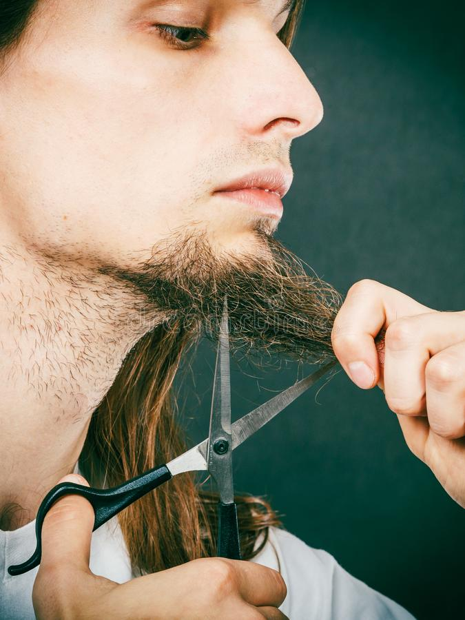 Man cutting his beard. Cut and shave concept. Young man with long beard holding scissors. Boy cutting hair on chin royalty free stock photo
