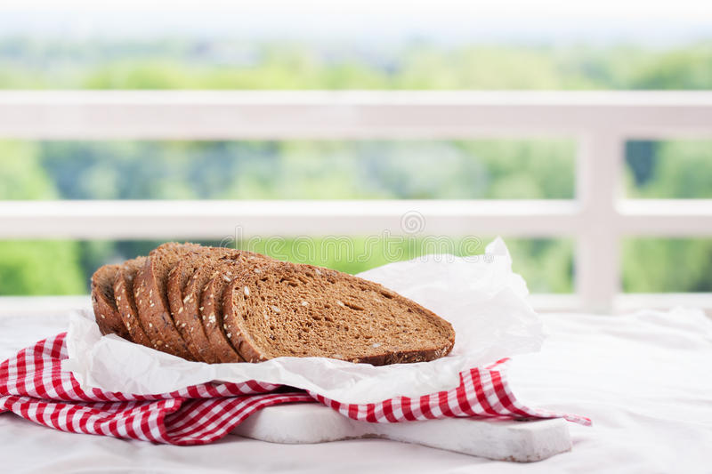 Cut in slices loaf of bread on a cut board on a kitchen background stock photos