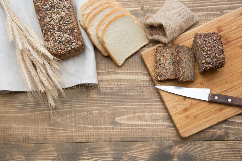 Fitness bread. A loaf of fresh rustic whole meal rye bread, sliced on a wooden board, rural food background. Top view. Copy space. royalty free stock images