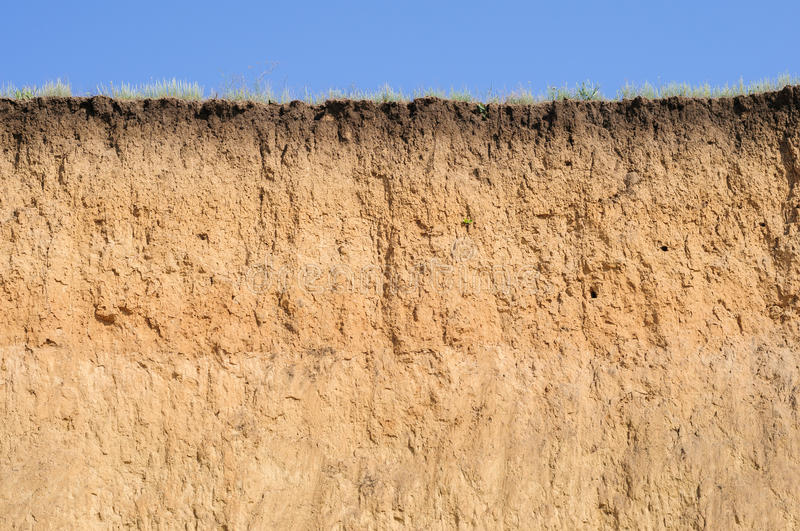Cut of soil with different layers, grass and sky. Cut of soil with different layers visible and grass on top stock photo