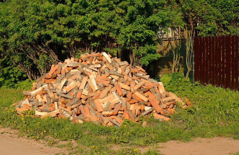 Cut and split firewood stacked in a pile near the house stock photo