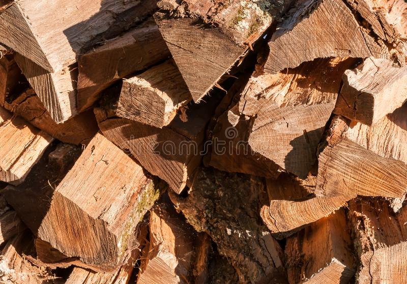 Cut and stacked logs of different sizes. In bright sunshine stock image