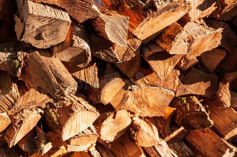 Cut and stacked logs of different sizes. In bright sunshine royalty free stock photo