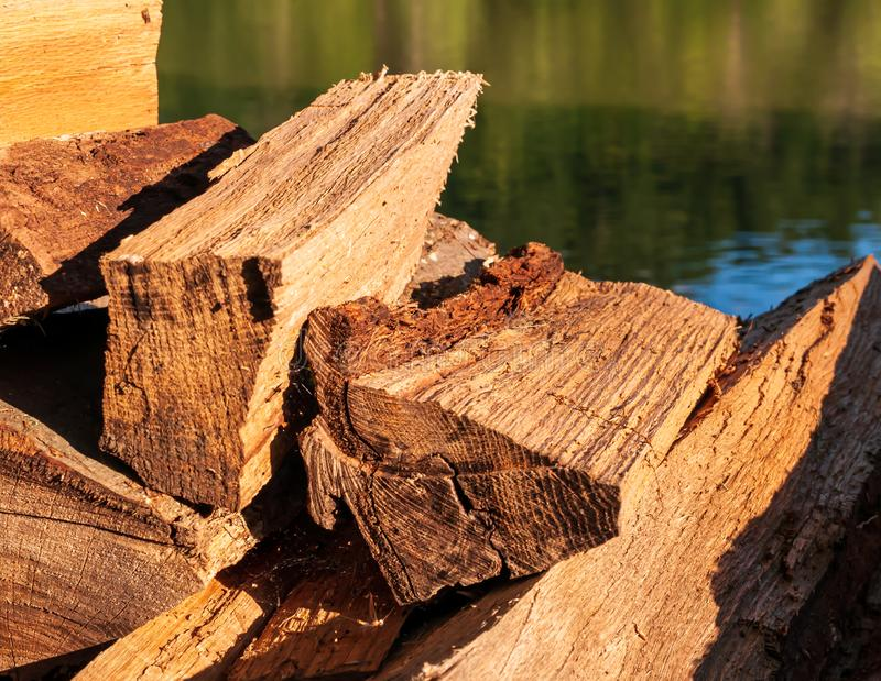 Cut and stacked logs of different sizes in bright sunshine. With a river in the background royalty free stock photo