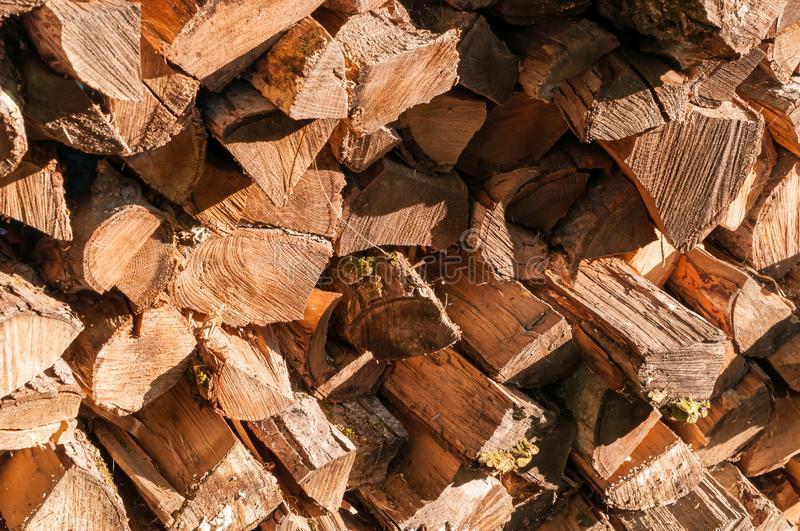 Cut and stacked logs of different sizes. In bright sunshine stock images