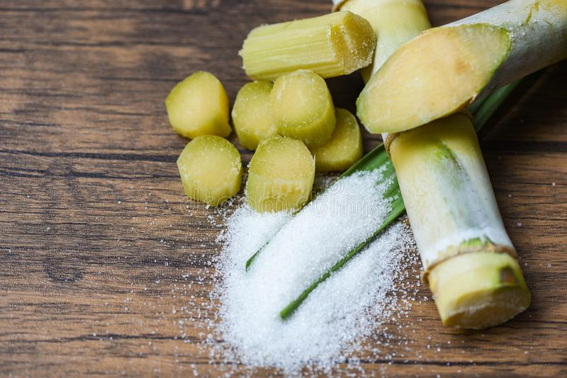 Cut sugar cane piece and white sugar wooden background top view royalty free stock photos
