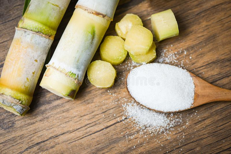 Cut sugar cane piece and white sugar wooden spoon background top view. Cut sugar cane piece and white sugar on wooden spoon background top view royalty free stock images