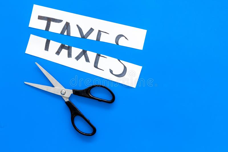 Cut taxes concept. Sciccors cut paper with word Taxes on blue background top view copy space stock image
