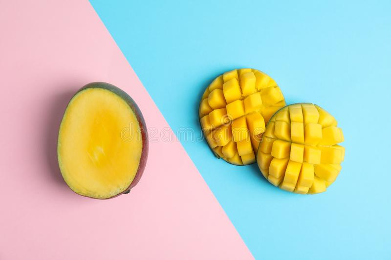 Cut tropical ripe mango on color background. Top view royalty free stock images