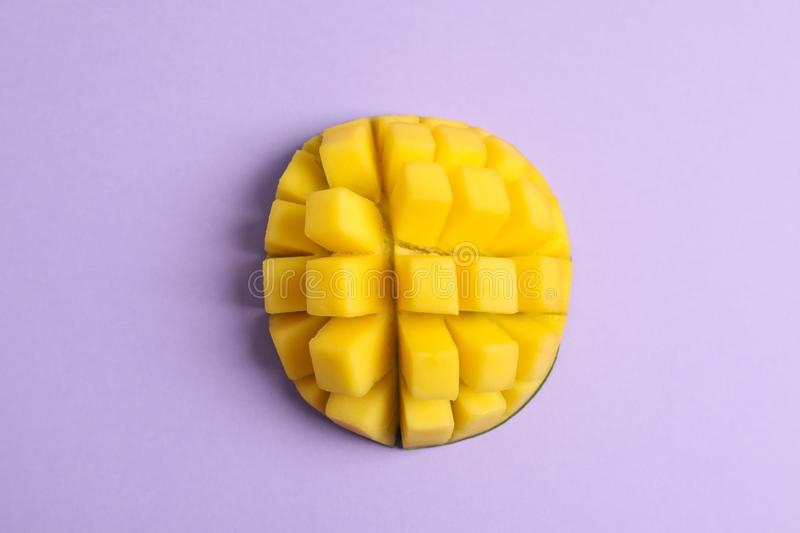 Cut tropical ripe mango on color background. Top view stock photo