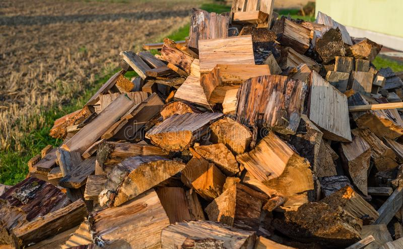 Cut trunks, a pile of firewood lying behind the house in the field. Cut trunks, a pile of firewood lying behind the house in the field stock photos