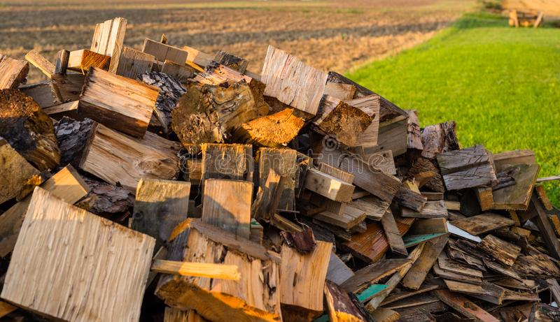 Cut trunks, a pile of firewood lying behind the house in the field. Cut trunks, a pile of firewood lying behind the house in the field royalty free stock image