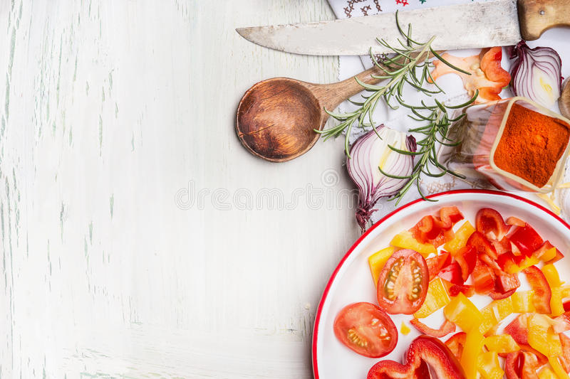 Cut vegetables , flavoring and herbs with cooking wooden spoon and kitchen knife on white wooden background, top view, border. H. Ealthy and vegetarian food or royalty free stock photos