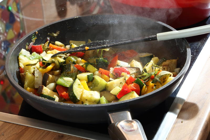 Cut Vegetables Frying in a Hot Pan. Assorted cut vegetables being cooked in a hot pan on the stove stock image