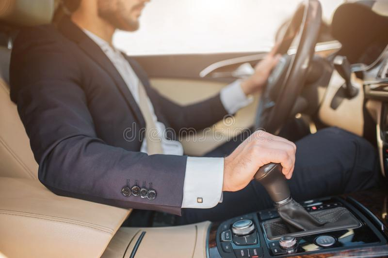 Cut view of bearded young man sitting in car and driving. He holds one hand on steering wheel and another one on royalty free stock photos