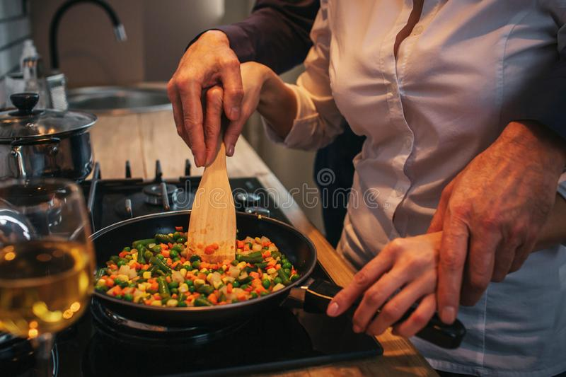 Cut view and close up. Man helping woman to cook dinner. He hold his handson hers. They stand together at stove. stock photos
