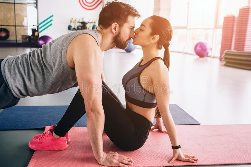 Cut view of a guy standing in a high plank position while his girlfriend is kissing him. It is so touchable and royalty free stock photos