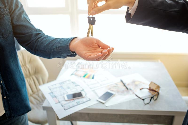 Cut view of man buying renting apartment. He reach hand and get keys from realtor. Apartment plans on table at window. Cut view of man buying renting apartment royalty free stock images