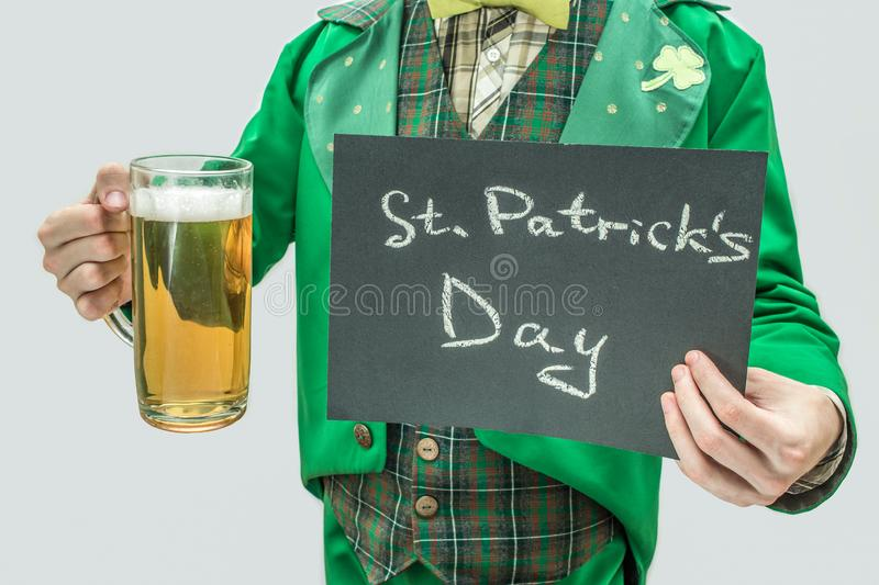 Cut view of man in green suit holding mug of beer and dark tablet with written words St. Patrick`s Day. on grey. Background stock images