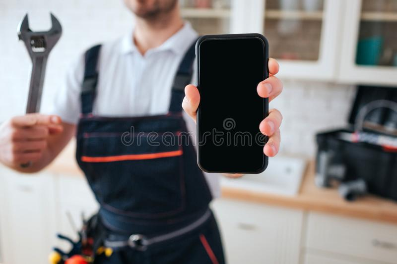 Cut view of man standing in kitchen. He hold wrench and phone in hands. Toolbox on desk behind. Daylight. stock photos