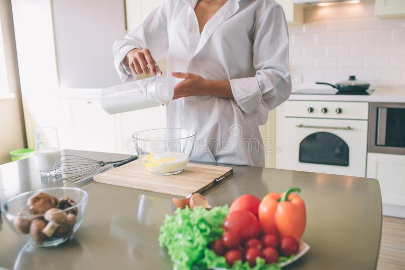 Cut view of oyung woman standing in kitchen and pouring milk into glass bowl. She is cooking. There is a lot of fresh stock images