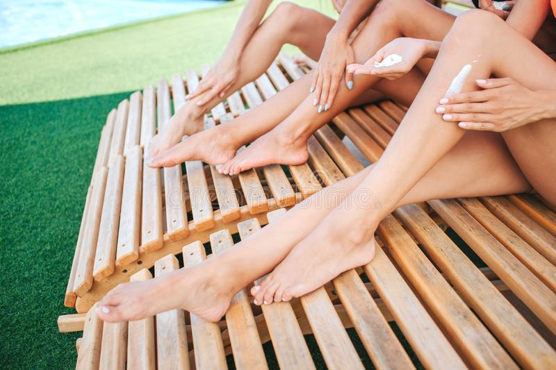 Cut view of slim and well-build young women`s legs. They have tan. Hands put some sun protection lotion on legs. Models royalty free stock photo