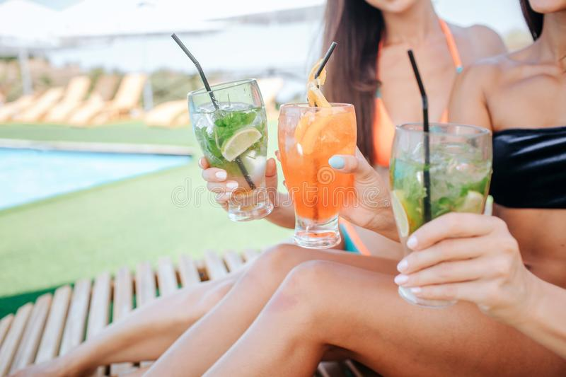 Cut view of three beautiful women sit on sunbeds and hold cocktails in hands. There are two green and one orange. Models royalty free stock images