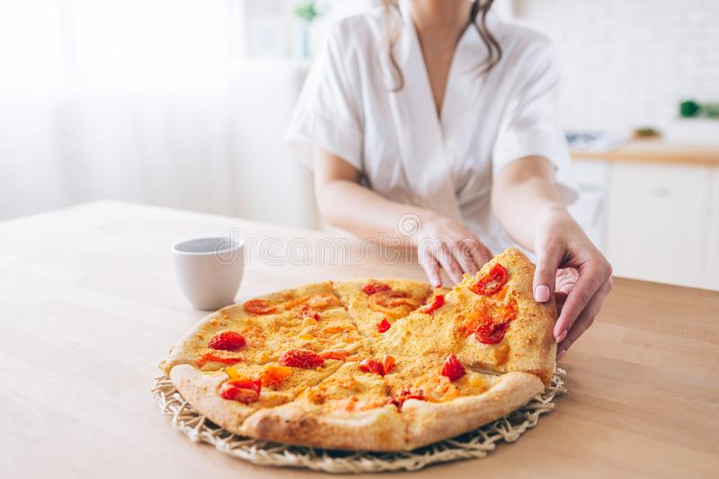 Cut view of woman in white dressing gown in kitchen. Taking piece of pizza. Small slice. Young housekeeper live carefree. Life royalty free stock photos
