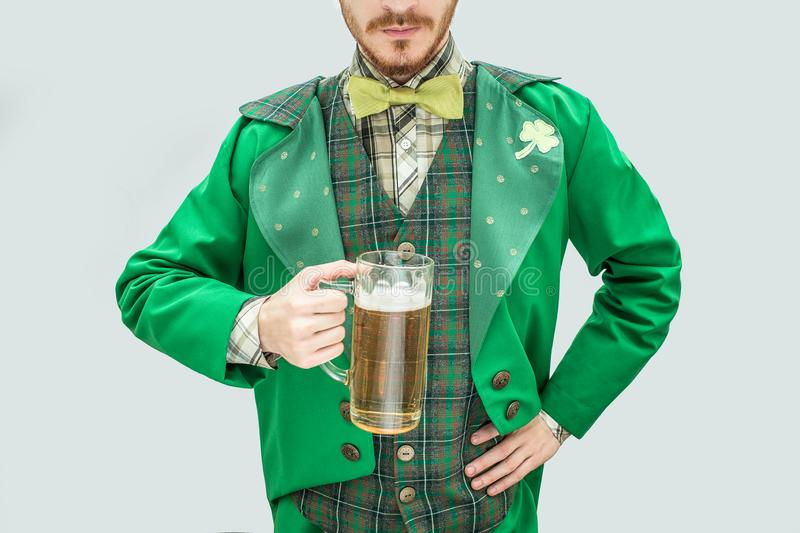 Cut view of young man in green suit holding mug of beer. He hold another hand on hips. Guy wear saint Patricks suit royalty free stock photography
