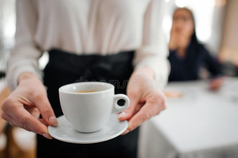 Cut view of young waitress holding cup of coffee in hands. Female customer sitting behind at table. They are in stock photo