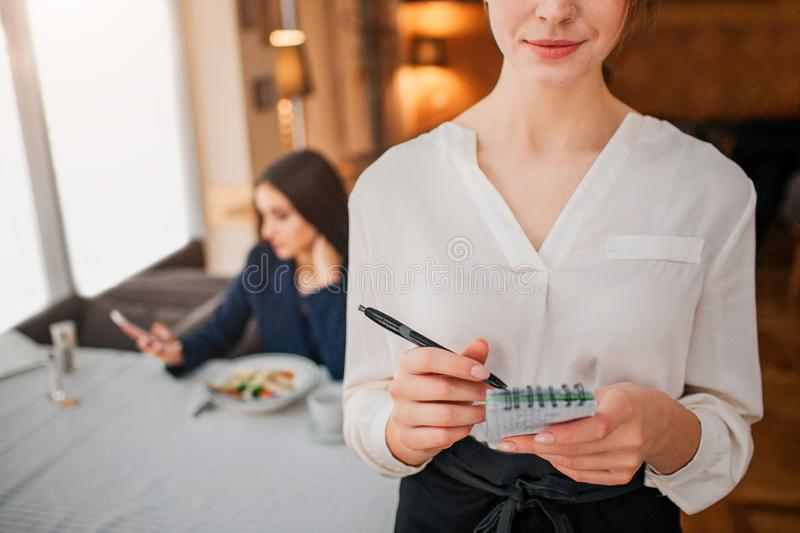 Cut view of young waitress write order into notebook. Female customer sit behind and look at phone. She wait for order. royalty free stock image
