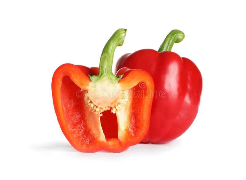 Cut and whole ripe red bell peppers. On white background royalty free stock photography