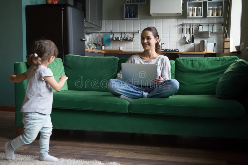 Cute active girl playing while mother using laptop at home. Cute active girl running over the room playing while young smiling single mother or sister using royalty free stock image
