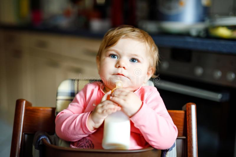 Cute adorable baby girl holding nursing bottle and drinking formula milk. First food for babies. New born child, sitting. In chair of domestic kitchen. Healthy stock image