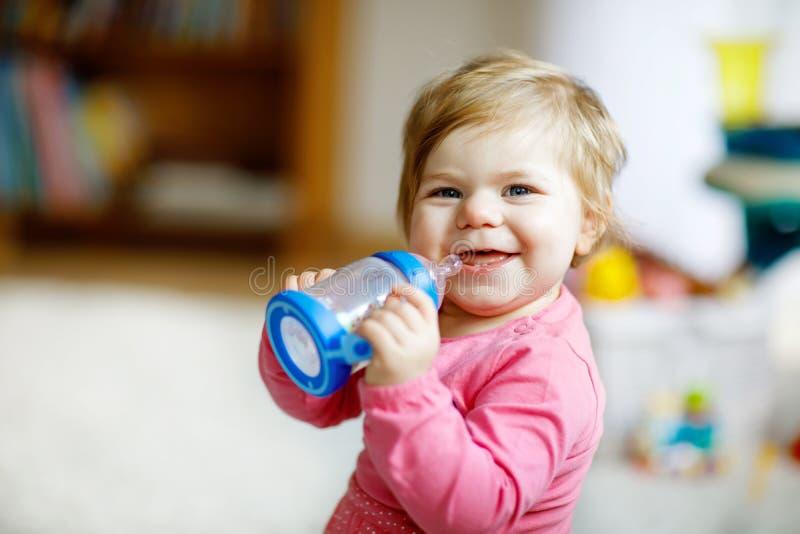 Cute adorable ewborn baby girl holding nursing bottle and drinking formula milk or water stock photos