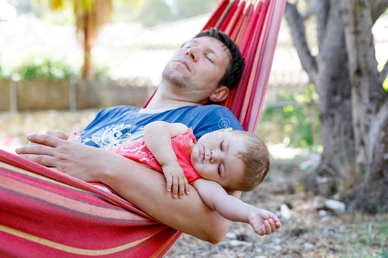 Cute adorable baby girl of 6 months and her father sleeping peaceful in hammock in outdoor garden. Closeup of beautiful royalty free stock image