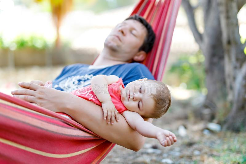 Cute adorable baby girl of 6 months and her father sleeping peaceful in hammock in outdoor garden stock photo