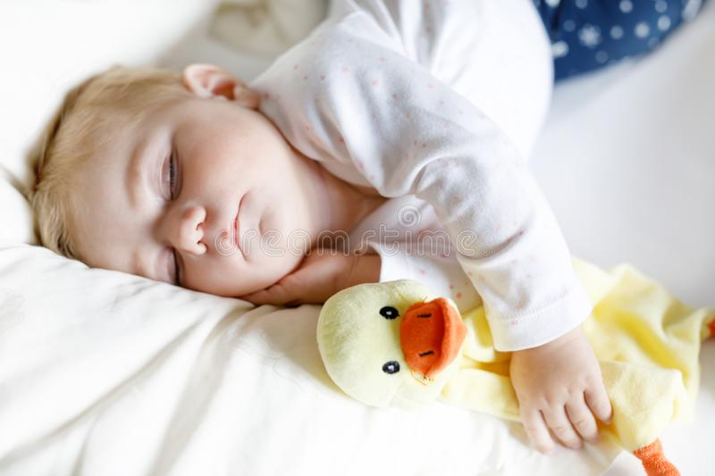 Cute adorable baby girl of 6 months sleeping peaceful in bed stock images