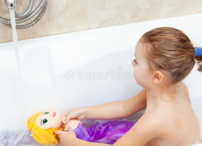 Female toddler takes a bath and plays with plastic toys royalty free stock images