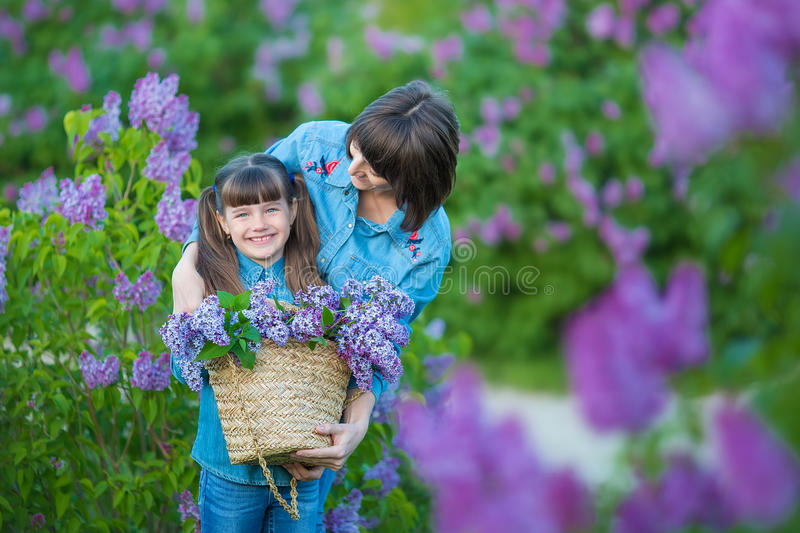 Cute adorable beautifull mother lady mom woman with brunette girl daughter in meadow of lilac purple bush.People in jeans wear. stock photography