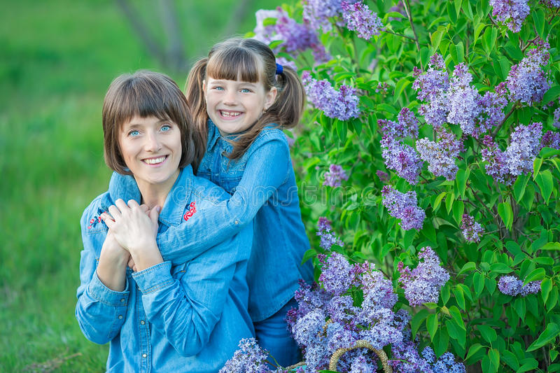 Cute adorable beautifull mother lady mom woman with brunette girl daughter in meadow of lilac purple bush.People in jeans wear. royalty free stock photography