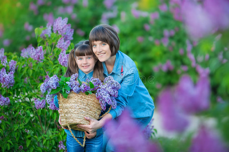Cute adorable beautifull mother lady mom woman with brunette girl daughter in meadow of lilac purple bush.People in jeans wear. stock photos